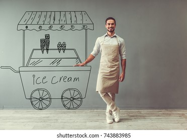 Handsome guy in apron is leaning on drawn ice cream cart, looking at camera and smiling while standing at the gray wall