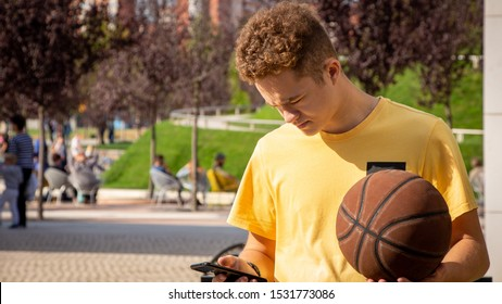 A handsome guy of athletic appearance is standing in a park with a ball. Kinky guy with a phone.