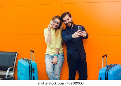 Handsome guy with beard in black shirt with pants is making selfie-portrait with pretty girl near on orange background between two suitcases. She has long hair, sweater, jeans and speaking on phone.