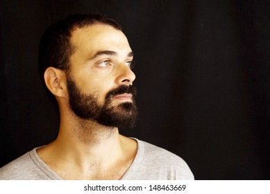 Handsome guy with beard and grey shirt on black background