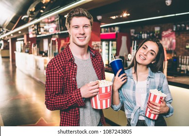 Handsome guy and beautiful girl are posing. They are looking straight and smiling. Guy has a basket of popcorn while girl is holding a cup of coke and basket of popcorn.