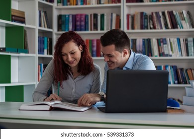 Handsome guy and beautiful redhead girl studying in the library and smiling. Opened laptop and book in front of them on the table and bookshelf full of books in the background.
