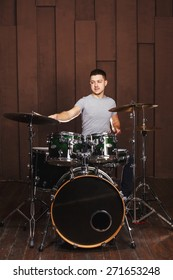 Handsome guy behind the drum kit on a brown background