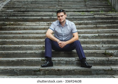 Handsome guy in blue shirt sitting alone on stairs