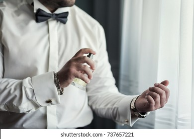 Handsome guy is choosing perfumes, Elegant man in suit using cologne,groom getting ready in the morning before wedding ceremony