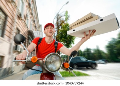 Handsome guy delivers Italian pizza. Broad smile of the restaurant courier driving a bike and holding paper boxes. Order food by phone.