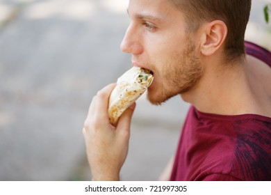 Handsome guy eating shawarma on the picnic. Close-up of happy man with fast food.