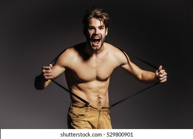 Handsome guy fashion sexy young bearded macho man model with suspenders on pants has bare muscular torso and happy surprised face holds on grey background