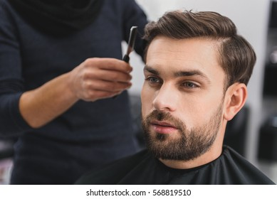 Handsome guy getting haircut by barber