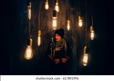 handsome guy hipster musician guitarist singer black hair, in the foreground the bright shiny hanging lamp in the dark