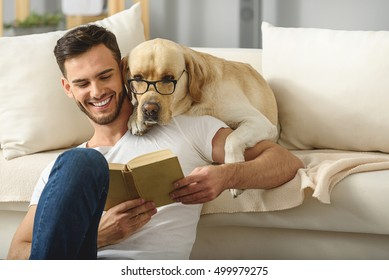 handsome guy holding book while smart pet read it