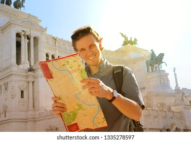 Handsome guy holding a city map looking at the camera and smiling at the beautiful sunny day at the Rome, Italy. The famous Vittorio Emanuele II monument at Piazza Venezia