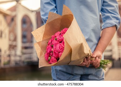 Handsome guy is holding flowers behind his back and waiting for his girlfriend, cropped