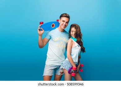 Handsome guy is hugging pretty girl with long hair on blue background in studio.They hold skateboards and have fun together.