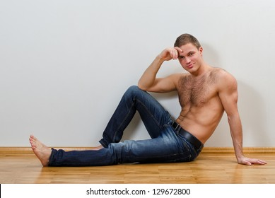 Handsome guy in jeans with bare torso sitting on the floor near the wall