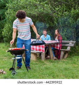 Handsome guy making a barbecue for his friends. Soft focus, high ISO, grainy image.