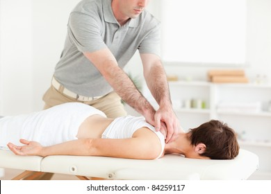 Handsome Guy massaging a cute woman's neck in a room