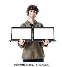 an handsome guy, maybe a student, in casual clothing showing two laptops with blank monitors