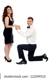 Handsome guy on his knees proposing girl to marry him holding hands of his  beloved