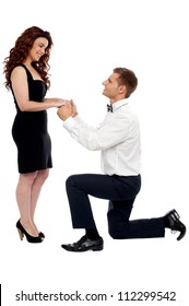 Handsome guy on knees proposing girl. Will you marry me?