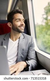 Handsome guy on train using laptop, smiling