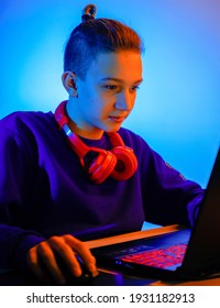 Handsome guy plays online games. Portrait of a gamer in neon light