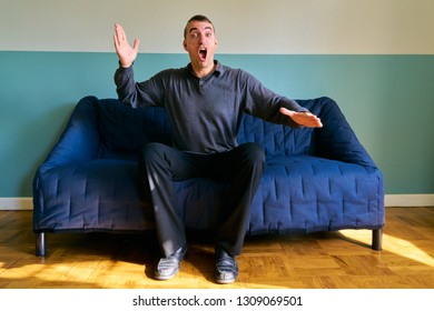 Handsome guy posing - upset caucasian man sitting on sofa and swinging his hand violently
