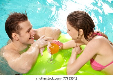 Handsome guy and pretty girl looking at one another in swimming pool