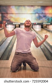 Handsome guy is raising hands in fists and smiling while standing on his knees on bowling alley