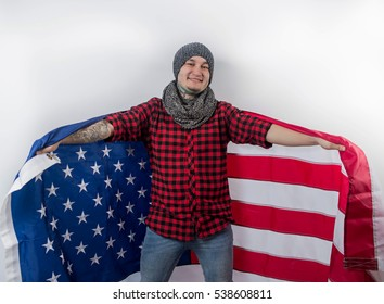 handsome guy in red shirt jeans grey hat scarf to the tattoo holds an American flag looking at camera smiling laughing isolate white background