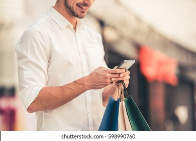 Handsome guy with shopping bags is using a mobile phone and smiling while doing shopping in the mall