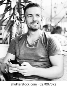 Handsome guy sitting at cafe bar, listening music and looking aside. He is holding mobile phone and smiling. Black and white photo with shallow depth of field.