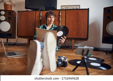 Handsome guy sitting on the floor and holding vinyl record stock photo