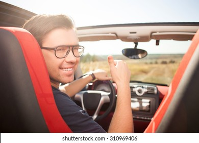 Handsome guy is sitting at steering wheel of his car. He is looking back and winking. The driver is smiling and giving thumb up