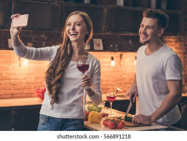 Handsome guy is smiling and cooking in the kitchen while his girlfriend is doing selfie using a smart phone