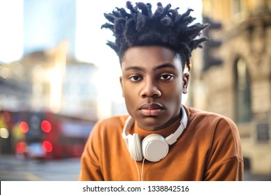Handsome guy standing in the street, listening music