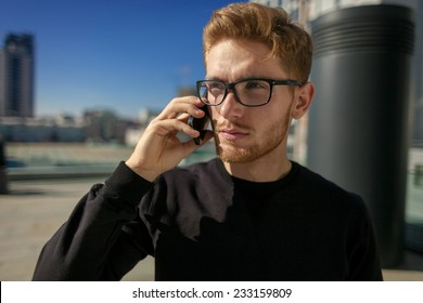 Handsome guy talking by cellphone on urban street.