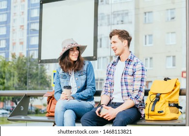Handsome guy trying to get acquainted with pretty girl at bus stop. Man and woman travelers with backpacks drinking coffee, talking while sits on bench of bus station.