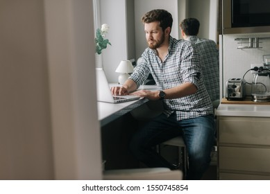 Handsome guy is typing on her laptop sitting next to a window in the kitchen.Concept of everyday life.