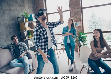 Handsome guy wearing, using VR-headset of virtual reality, gesticulating, touching something with arm in office during coffee break, four colleagues laughing, having fun