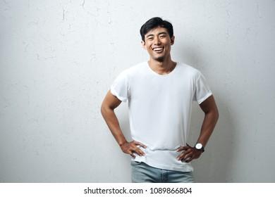 Handsome guy in white blank t-shirt, grunge wall, horizontal studio portrait