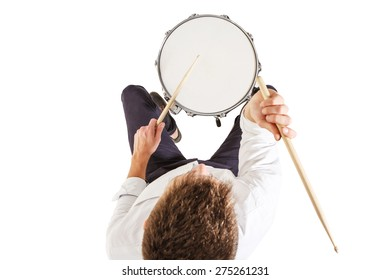 Handsome guy in a white shirt teaches properly play the drums on a white background