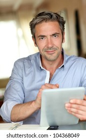 Handsome guy working from home with electronic tablet