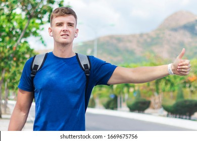 Handsome guy, young man traveler trying to stop, catch taxi car, cab. Boy standing near road with backpack, wireless earphones holding out his hand with thumb up, hitchhiking sign. Hitchhiker, summer