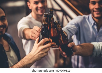 Handsome guys are clinking bottles of beer and smiling while resting in pub