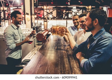 Handsome guys are drinking beer, talking with waiter and smiling while resting in pub