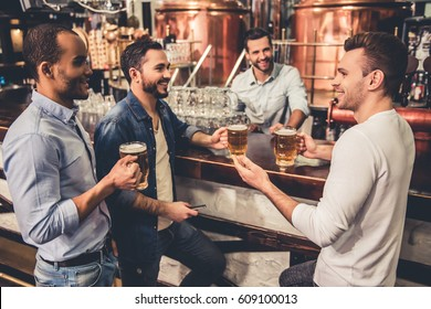 Handsome guys are drinking beer, talking and smiling while resting in pub