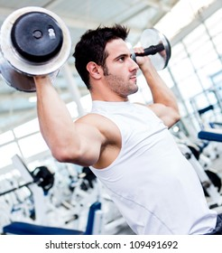 Handsome gym man lifting heavy free weights