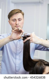 A handsome hairdresser making a haircut for a brunette girl