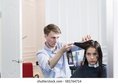 Handsome hairdresser making a haircut for a brunette girl